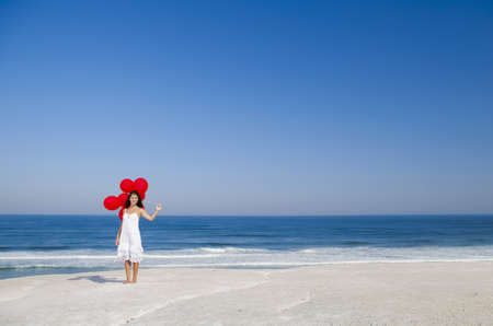 Beautiful girl with red ballons in the beach Stock Photo - 18971865