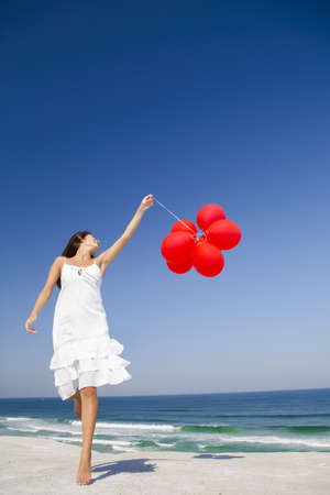Beautiful girl jumping with red ballons in the beach  Stock Photo - 18971904
