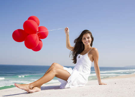 Beautiful girl with red ballons sitting in the beach  Stock Photo - 18971891