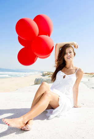 Beautiful girl with red ballons sitting in the beach  photo