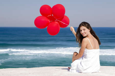 Beautiful girl with red ballons sitting in the beach  Stock Photo - 18971890