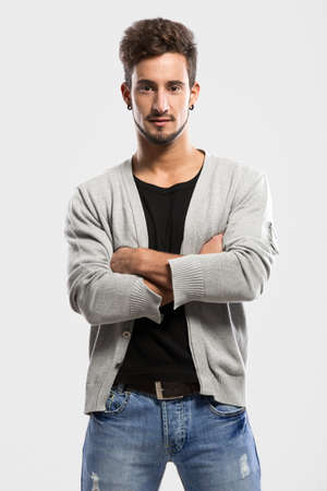 Handsome young man with hands folded, over a gray background Stock Photo