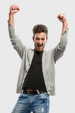 Happy young man with arms up, over a gray background Stock Photo - 18971861
