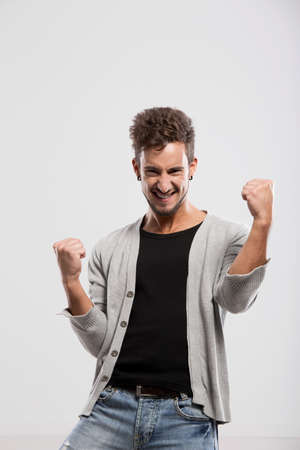 Happy young man with arms up, over a gray background Stock Photo - 18971894