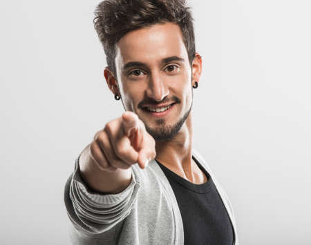 Handsome young man looking and pointing to the camera, over a gray background Stock Photo - 18971892