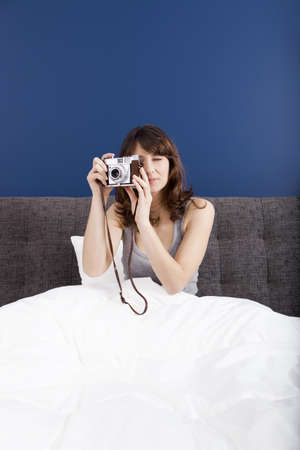 Young girl on the bed holding a photographic camara and shooting Stock Photo - 19428353