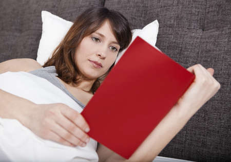 Beautiful young woman lying on the bed and reading a book Stock Photo - 19428413
