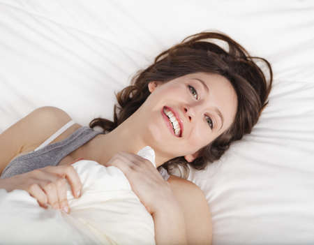 Beautiful and natural young girl on the bed laughing  Stock Photo - 19428417