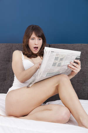 Happy young woman with a astonish expression reading the newspaper photo