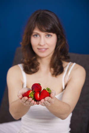 Beautiful and happy young woman holding strawberries with both hands photo