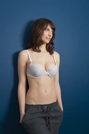 Beautiful young woman wearing a casual lingerie and pajama pants, against a blue wall Stock Photo - 19428351