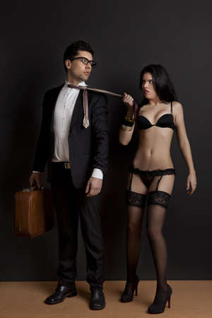 Sexy young woman grab the tie of the business man. Concept about work and pleasure photo