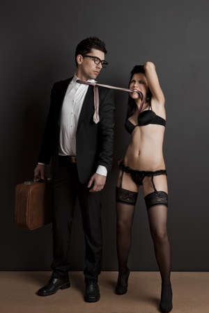 Business man and a sexy young woman biting is tie. Concept about work and pleasure photo