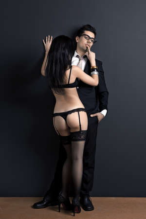 Business man and a sexy young woman in lingerie. Concept about work and pleasure Stock Photo