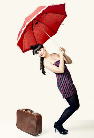 Beautiful woman with a vintage look posing with a red umbrella Stock Photo - 19428607