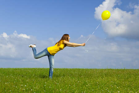Happy young woman with a yellow balloon on a green meadow Stock Photo - 19428637