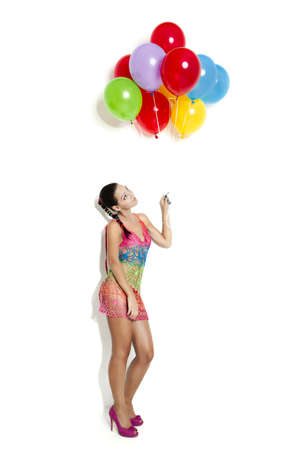 Fashion portrait of a beautiful young women posing with ballons, isolated on white photo
