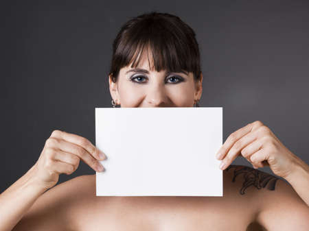 Beautiful woman holding a white billboard in front of the face photo