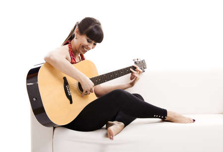 Beautiful woman sitting on the sofa and playing guitar, isolated on white photo