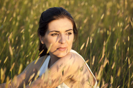 Outdoor portrait of a woman in a meadow on a summer day photo