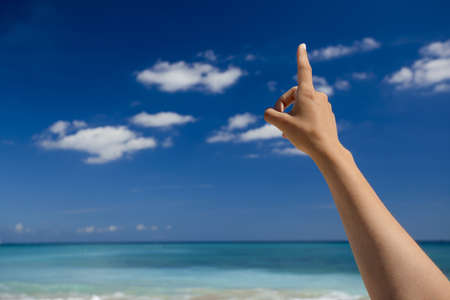 Female hand against a beautiful blue sky pointing somewhere Stock Photo - 19844874