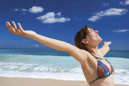 Beautiful young woman with arms open in a tropical beach enjoying the summer Stock Photo - 19844921