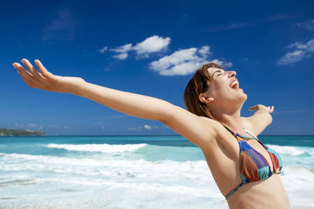 Beautiful young woman with arms open in a tropical beach enjoying the summer  photo