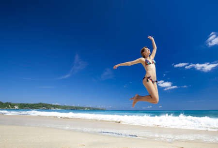 Beautiful and athletic young woman enjoying the summer, jumping in a tropical beach photo