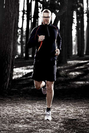 Athletic man doing exercise, running in the forest Stock Photo - 20340957