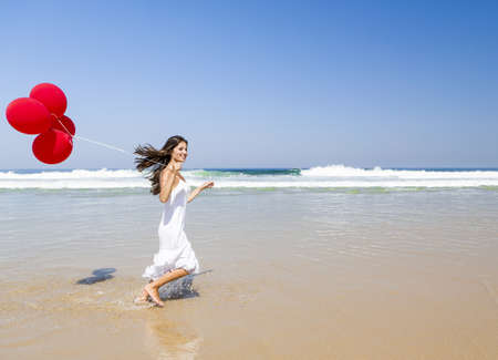ballons: Beautiful girl running in the beach with red ballons in her hand