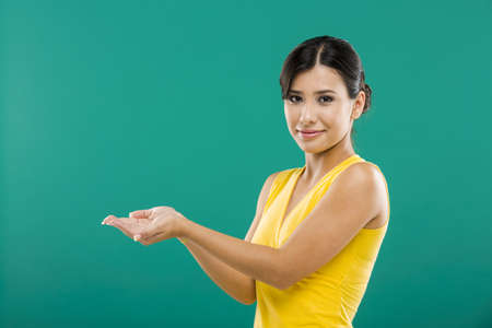 Beautiful asian woman showing the palm of the hands, over a green background