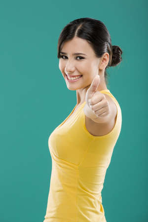 Beautiful and happy asian woman with thumbs up, over a green background photo