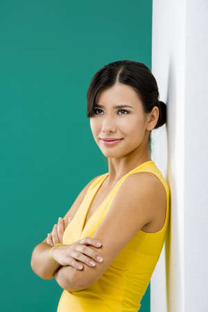 Beautiful and happy asian woman against a white wall in a green background photo