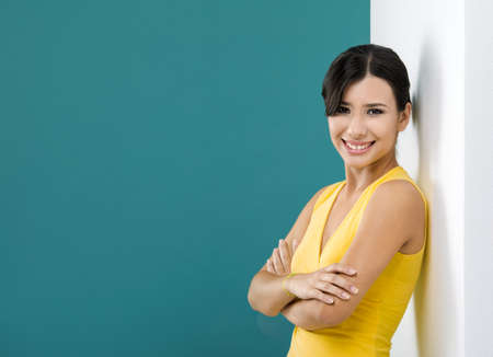 supported: Beautiful and happy asian woman against a white wall in a green background Stock Photo