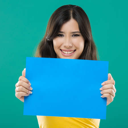 Beautiful asian woman holding a blue billboard, over a green background photo