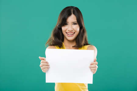 Beautiful asian woman holding a white billboard, over a green background photo