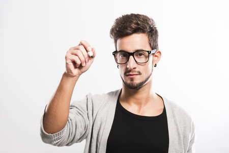Portrait of a handsome young man wearing glasses and  writting something on a glass writeboard photo