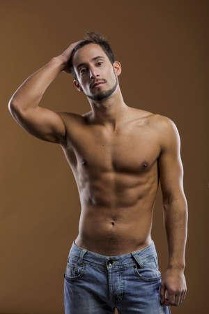 hombre flaco: Modelo masculino descamisado que presenta sobre un fondo marrón