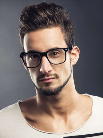 Casual portrait of a hansome young man wearing glasses, looking to the camera photo