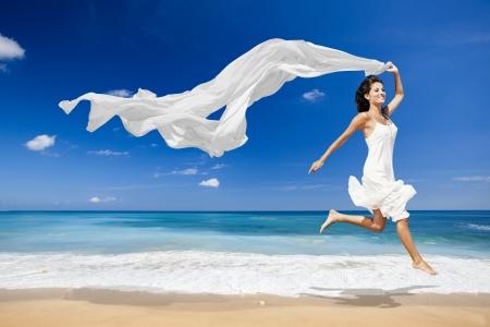 아름 다운 여자 실행 및 흰색 티슈로 해변에서 점프