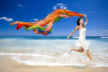 아름 다운 여자 실행 및 컬러 tisue와 함께 해변에서 점프