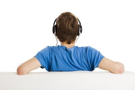 Joven sentado en el sof? y escuchar m?sica, aislados en blanco Foto de archivo - 21728382