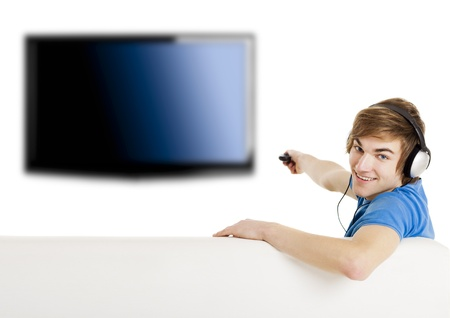 Young man sitting on the couch using a remote control and watching tv Фото со стока