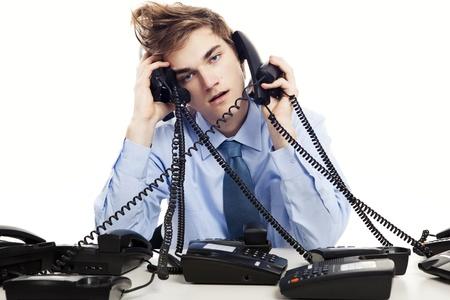 Jonge man zitten in het kantoor en het beantwoorden van verschillende telefoons op hetzelfde moment
