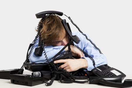 携帯電話の束彼の上に座って疲れきった男