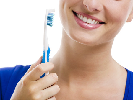 Beautiful woman with a great smile holding toothbrush, isolated over a white background
