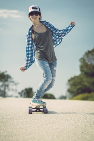 Young woman down the road with a skateboard