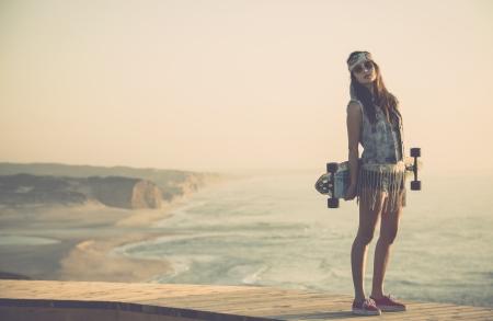 Beautiful and fashion young woman posing with a skateboard Фото со стока