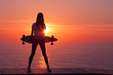 Beautiful and fashion young woman posing at teh sunset with a skateboard Stock Photo