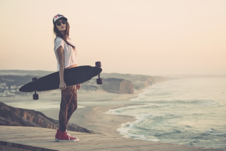 Beautiful and fashion young woman posing with a skateboard Stock Photo